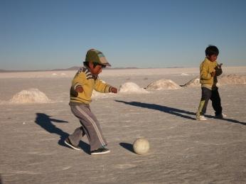 Enfant jouant au foot dans le désert de sel